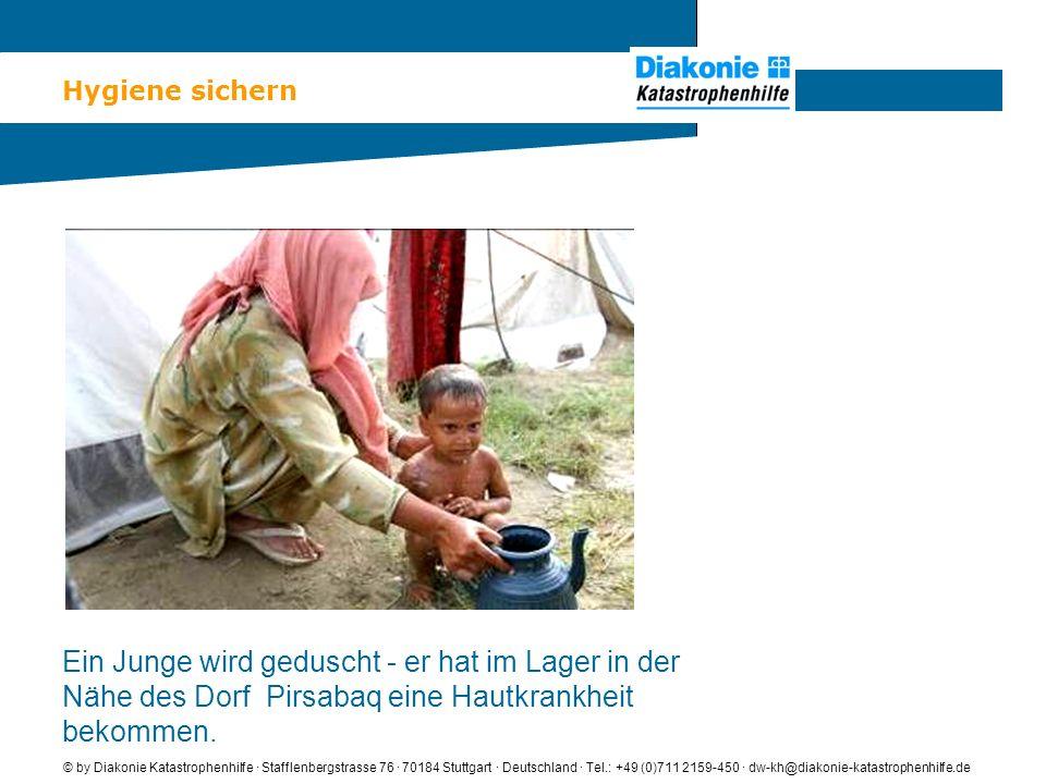 Hygiene sichern © by Diakonie Katastrophenhilfe · Stafflenbergstrasse 76 · 70184 Stuttgart · Deutschland · Tel.: +49 (0)711 2159-450 · dw-kh@diakonie-katastrophenhilfe.de Ein Junge wird geduscht - er hat im Lager in der Nähe des Dorf Pirsabaq eine Hautkrankheit bekommen.