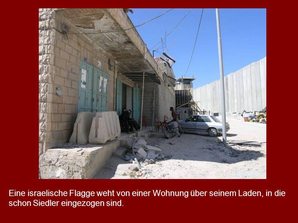 Eine israelische Flagge weht von einer Wohnung über seinem Laden, in die schon Siedler eingezogen sind.