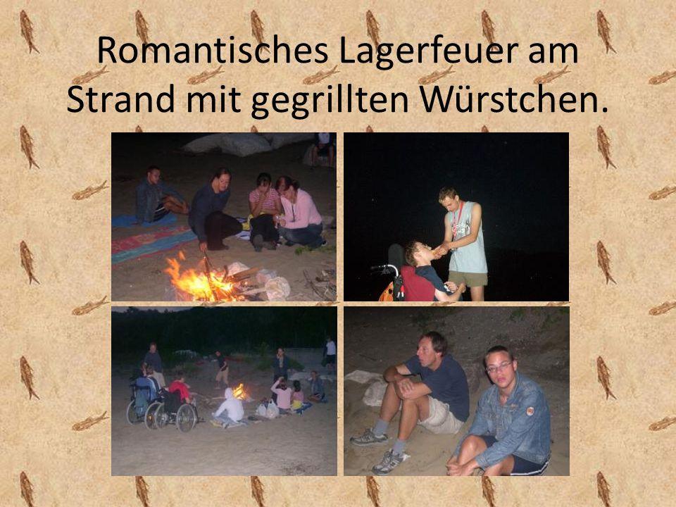 Romantisches Lagerfeuer am Strand mit gegrillten Würstchen.