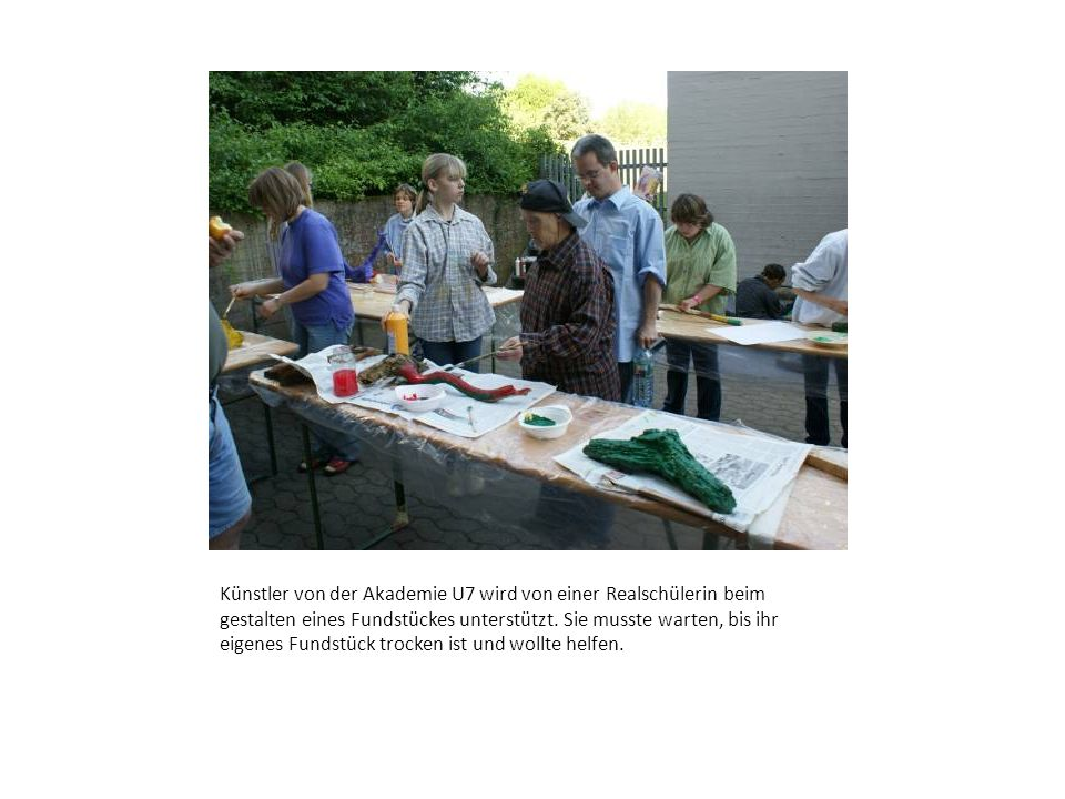 Künstler von der Akademie U7 wird von einer Realschülerin beim gestalten eines Fundstückes unterstützt. Sie musste warten, bis ihr eigenes Fundstück t