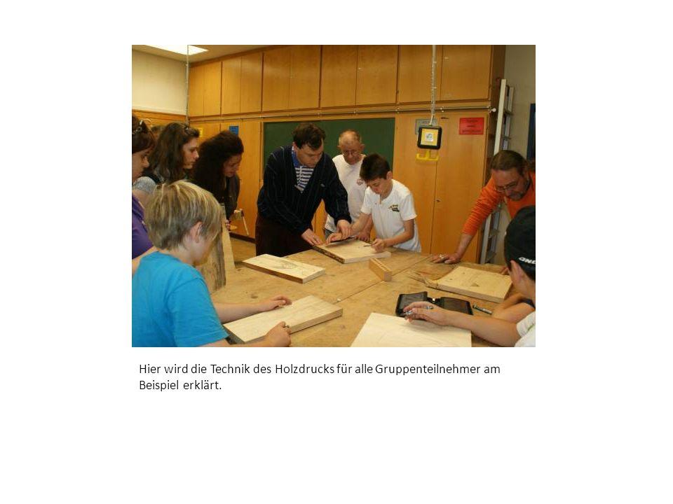 Hier wird die Technik des Holzdrucks für alle Gruppenteilnehmer am Beispiel erklärt.