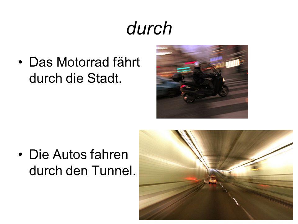durch Das Motorrad fährt durch die Stadt. Die Autos fahren durch den Tunnel.