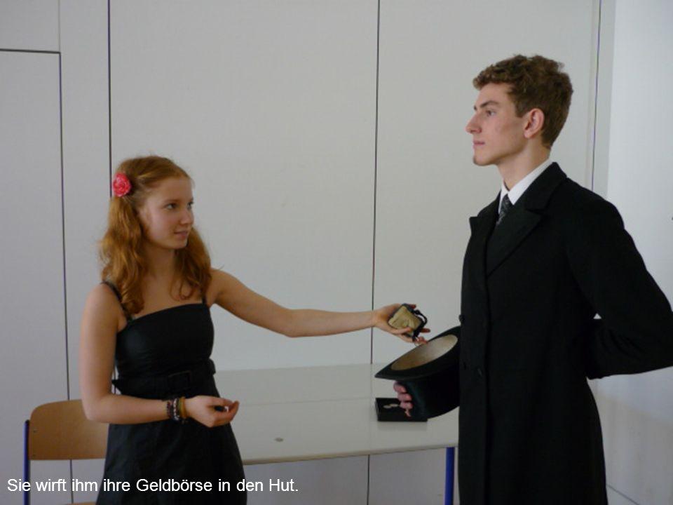 Sie wirft ihm ihre Geldbörse in den Hut.