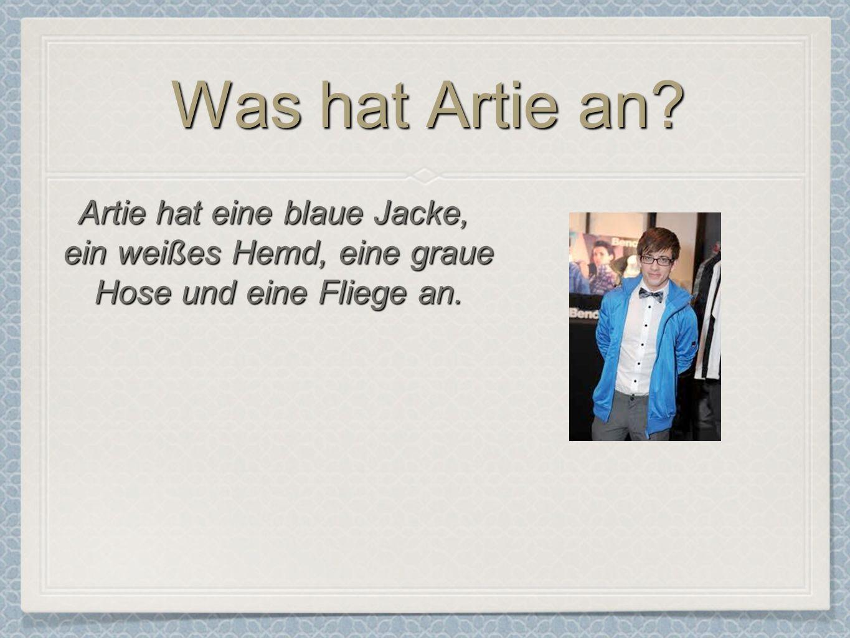 Was hat Artie an? Artie hat eine blaue Jacke, ein weißes Hemd, eine graue Hose und eine Fliege an.