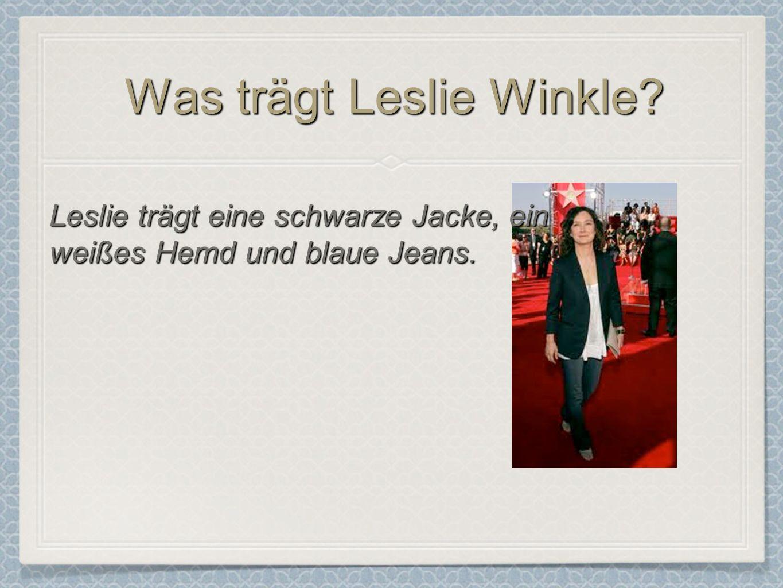 Was trägt Leslie Winkle? Leslie trägt eine schwarze Jacke, ein weißes Hemd und blaue Jeans.