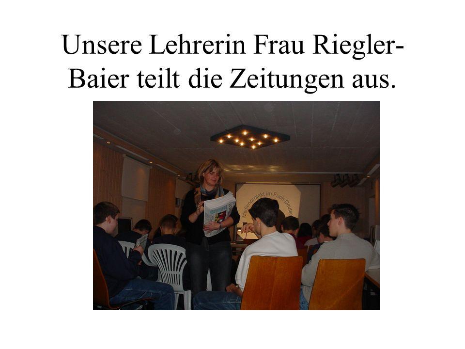 Unsere Lehrerin Frau Riegler- Baier teilt die Zeitungen aus.