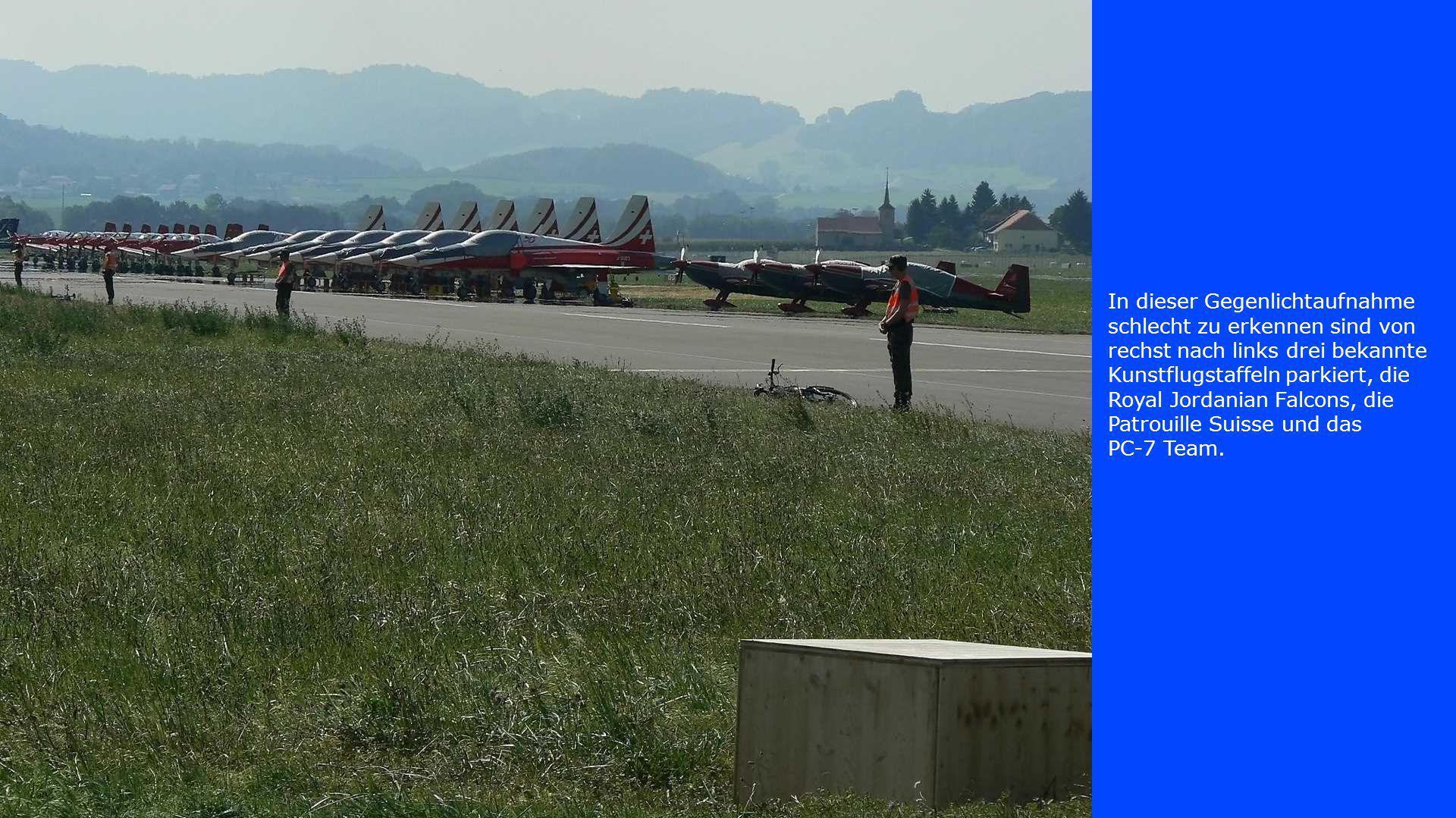 In dieser Gegenlichtaufnahme schlecht zu erkennen sind von rechst nach links drei bekannte Kunstflugstaffeln parkiert, die Royal Jordanian Falcons, die Patrouille Suisse und das PC-7 Team.