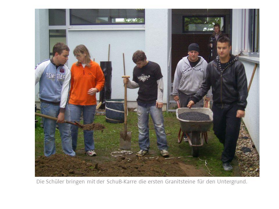 Die Schüler bringen mit der SchuB-Karre die ersten Granitsteine für den Untergrund.