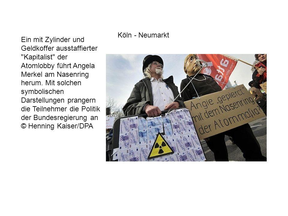 Ein mit Zylinder und Geldkoffer ausstaffierter Kapitalist der Atomlobby führt Angela Merkel am Nasenring herum.