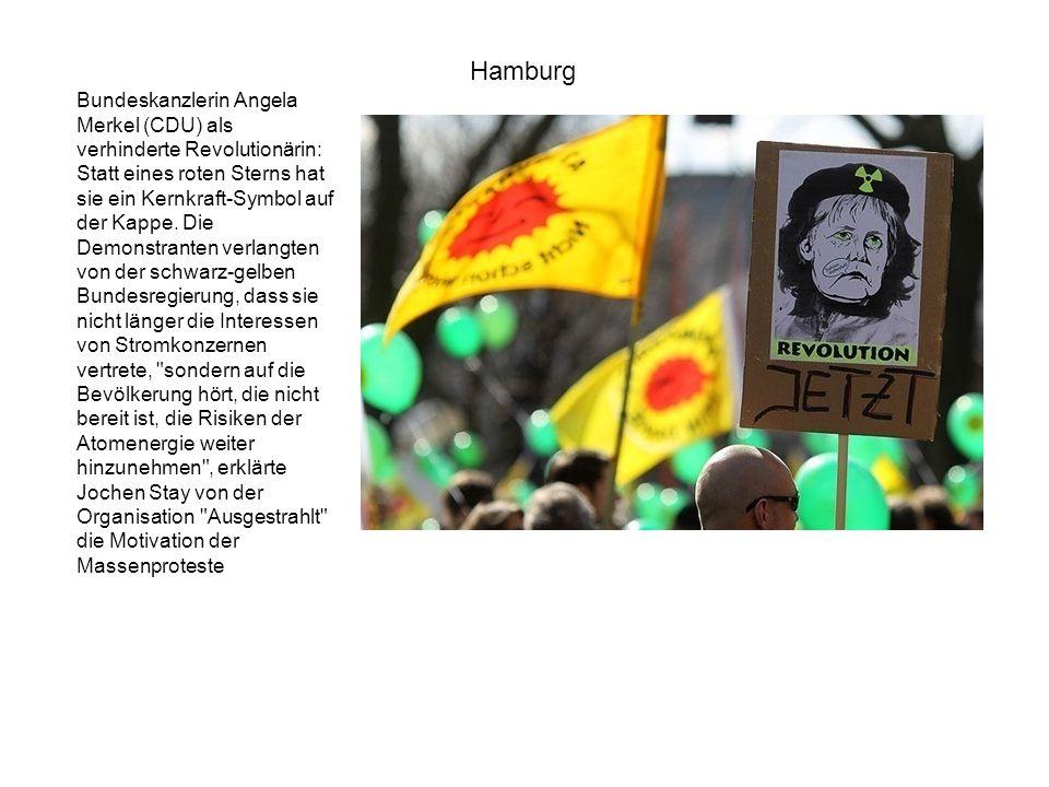 Bundeskanzlerin Angela Merkel (CDU) als verhinderte Revolutionärin: Statt eines roten Sterns hat sie ein Kernkraft-Symbol auf der Kappe. Die Demonstra