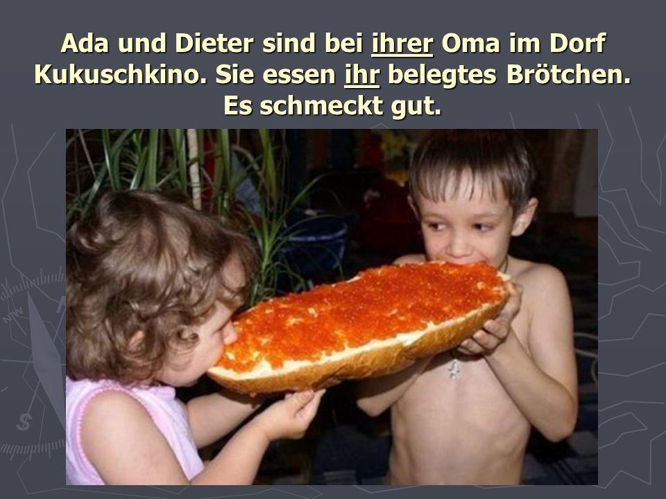 Ada und Dieter sind bei ihrer Oma im Dorf Kukuschkino. Sie essen ihr belegtes Brötchen. Es schmeckt gut.