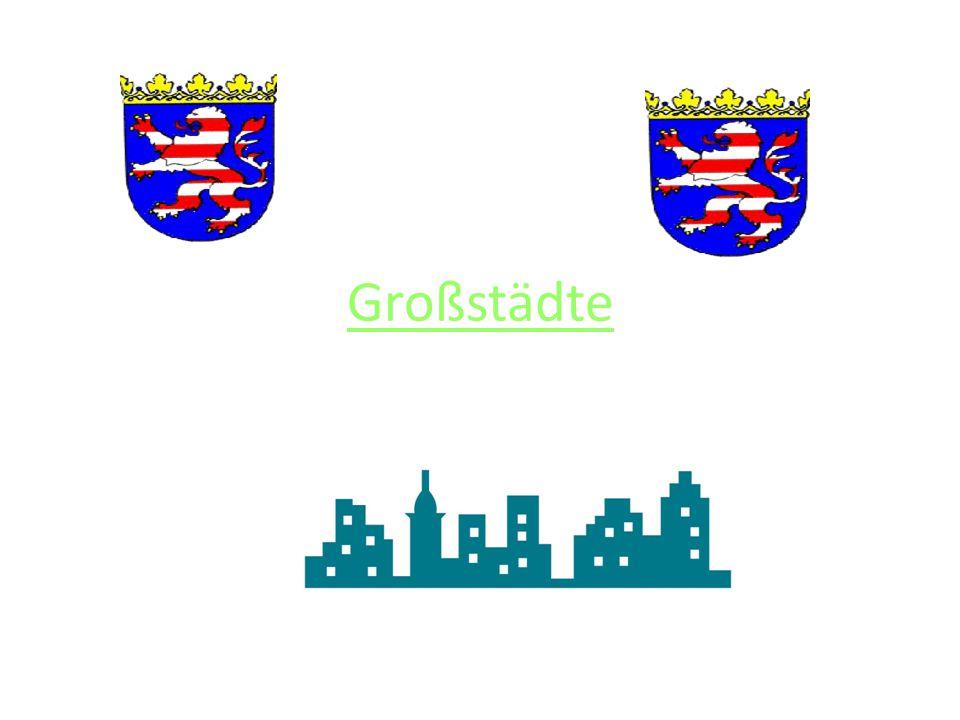 """Fulda Das ist das Wappen von Fulda """"Ein gespaltener Schild; vorne in Silber ein schwarzes, durchgehendes Kreuz, hinten in Rot ein grüner Drei berg, aus dem eine grüne Lilienstaude mit drei silbernen Blüten herauswächst."""