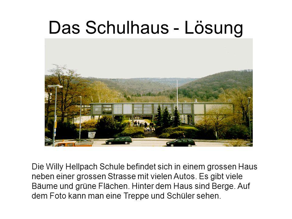 Das Schulhaus - Lösung Die Willy Hellpach Schule befindet sich in einem grossen Haus neben einer grossen Strasse mit vielen Autos. Es gibt viele Bäume