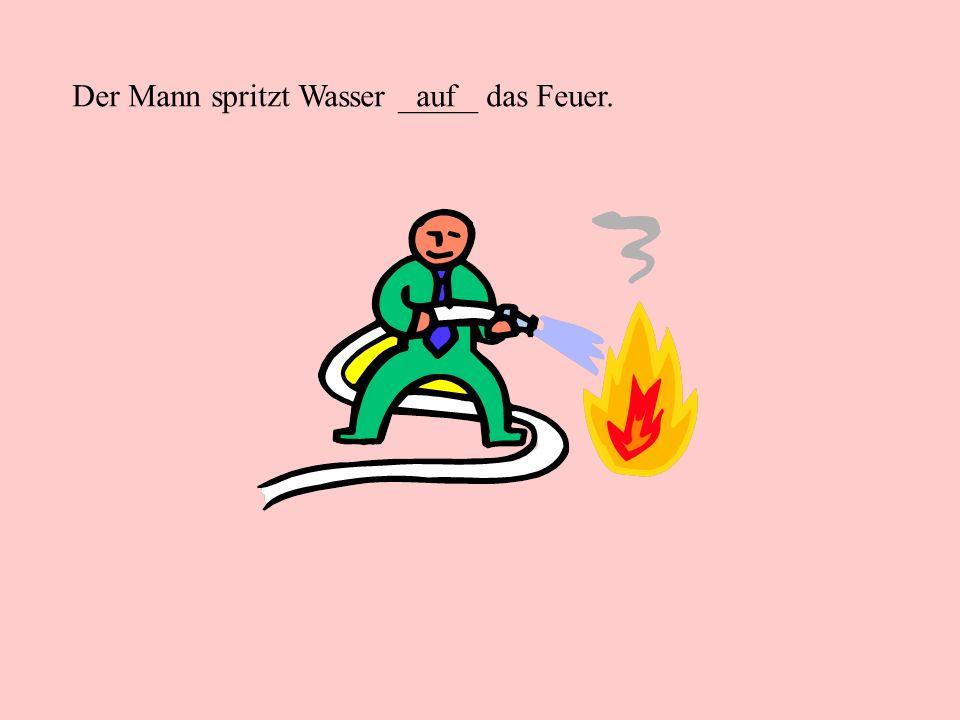 Der Mann spritzt Wasser _____ das Feuer.auf