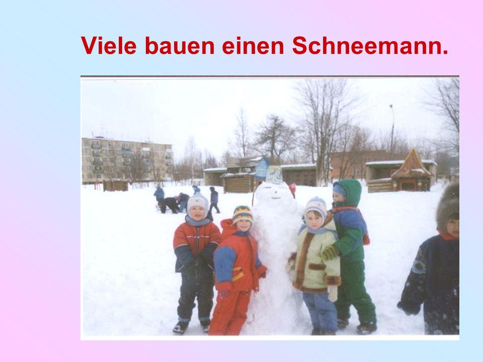 Viele bauen einen Schneemann.