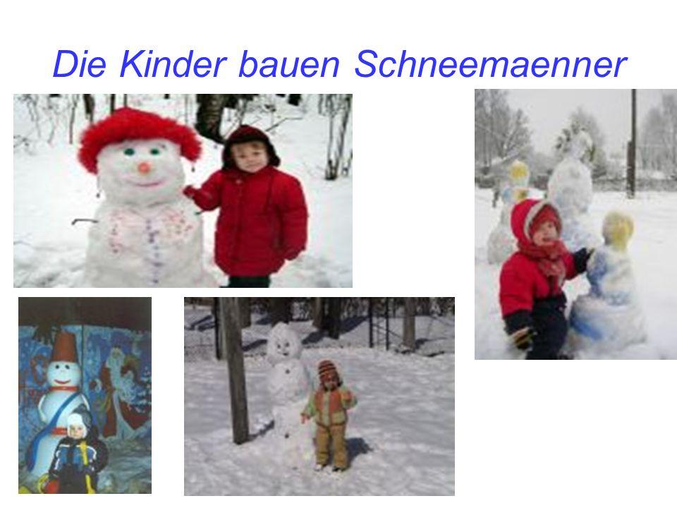 Die Kinder bauen Schneemaenner