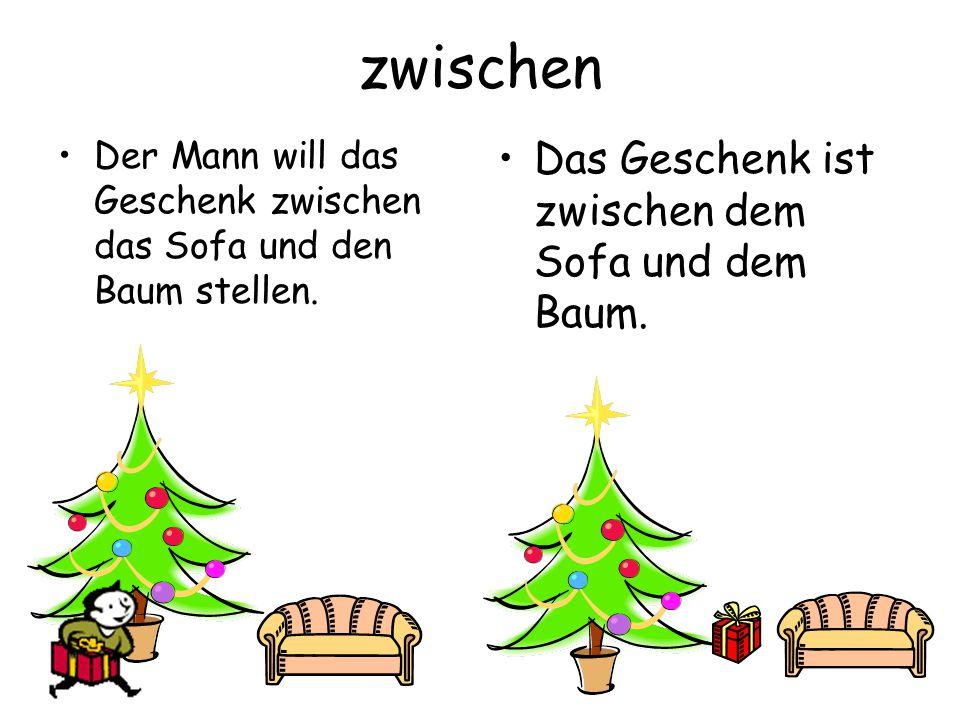 zwischen Der Mann will das Geschenk zwischen das Sofa und den Baum stellen.