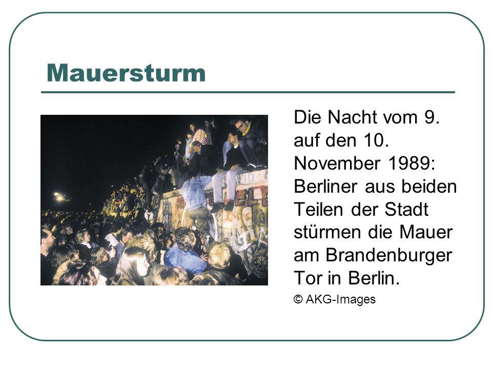 Mauersturm Die Nacht vom 9. auf den 10. November 1989: Berliner aus beiden Teilen der Stadt stürmen die Mauer am Brandenburger Tor in Berlin. © AKG-Im