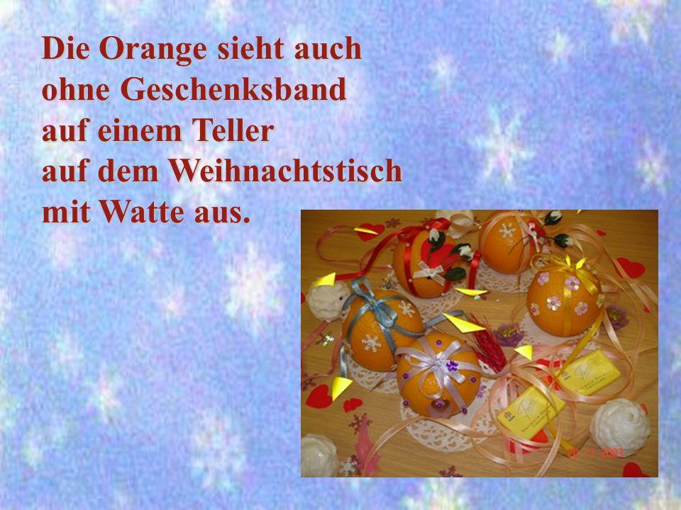 Die Orange sieht auch ohne Geschenksband auf einem Teller auf dem Weihnachtstisch mit Watte aus.
