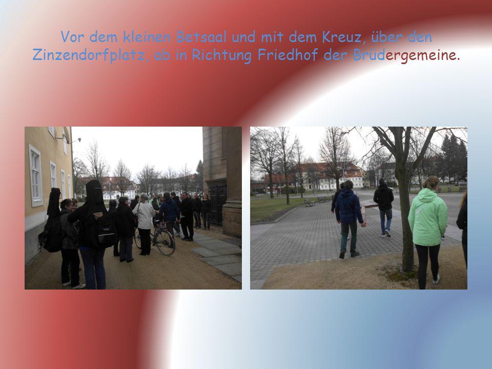Vor dem kleinen Betsaal und mit dem Kreuz, über den Zinzendorfplatz, ab in Richtung Friedhof der Brüdergemeine.