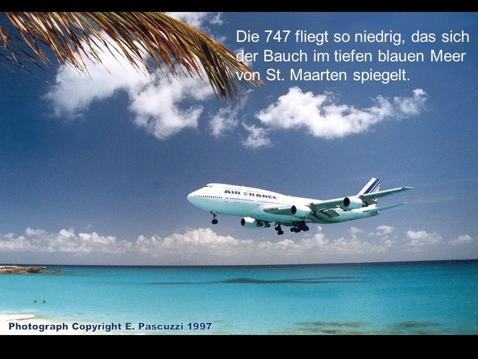 Die 747 fliegt so niedrig, das sich der Bauch im tiefen blauen Meer von St. Maarten spiegelt.