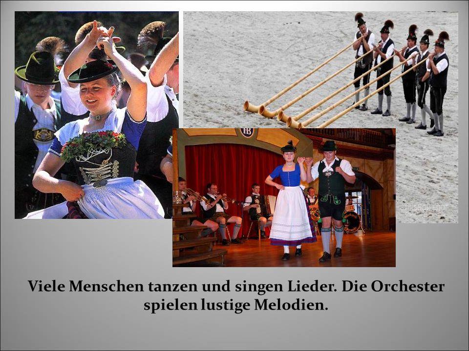 Viele Menschen tanzen und singen Lieder. Die Orchester spielen lustige Melodien.