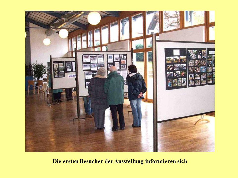 Die ersten Besucher der Ausstellung informieren sich