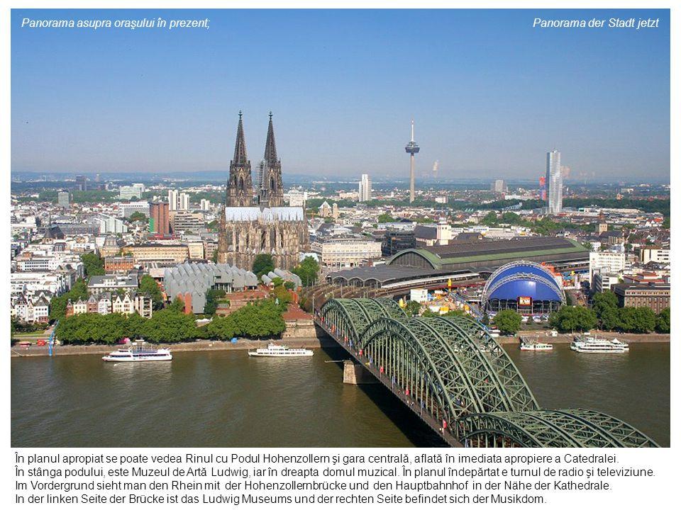În planul apropiat se poate vedea Rinul cu Podul Hohenzollern şi gara centrală, aflată în imediata apropiere a Catedralei. În stânga podului, este Muz