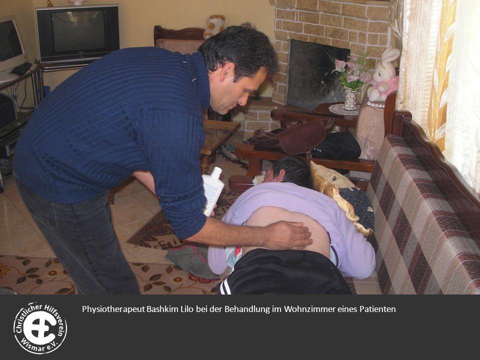 Physiotherapeut Bashkim Lilo bei der Behandlung im Wohnzimmer eines Patienten