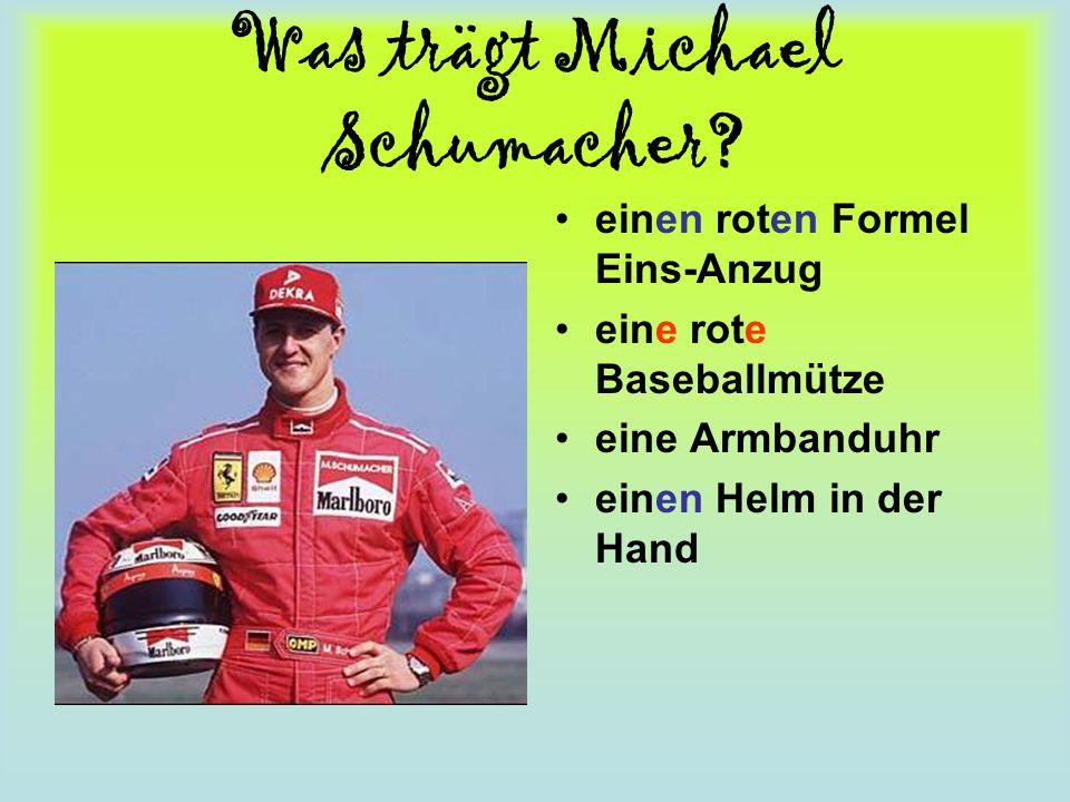 Was trägt Michael Schumacher? einen roten Formel Eins-Anzug eine rote Baseballmütze eine Armbanduhr einen Helm in der Hand
