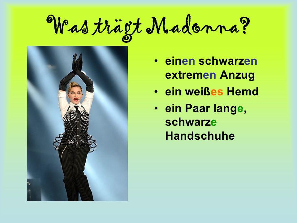 Was trägt Madonna? einen schwarzen extremen Anzug ein weißes Hemd ein Paar lange, schwarze Handschuhe