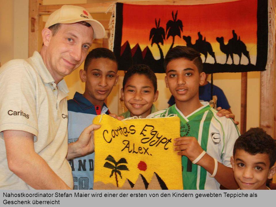 Nahostkoordinator Stefan Maier wird einer der ersten von den Kindern gewebten Teppiche als Geschenk überreicht