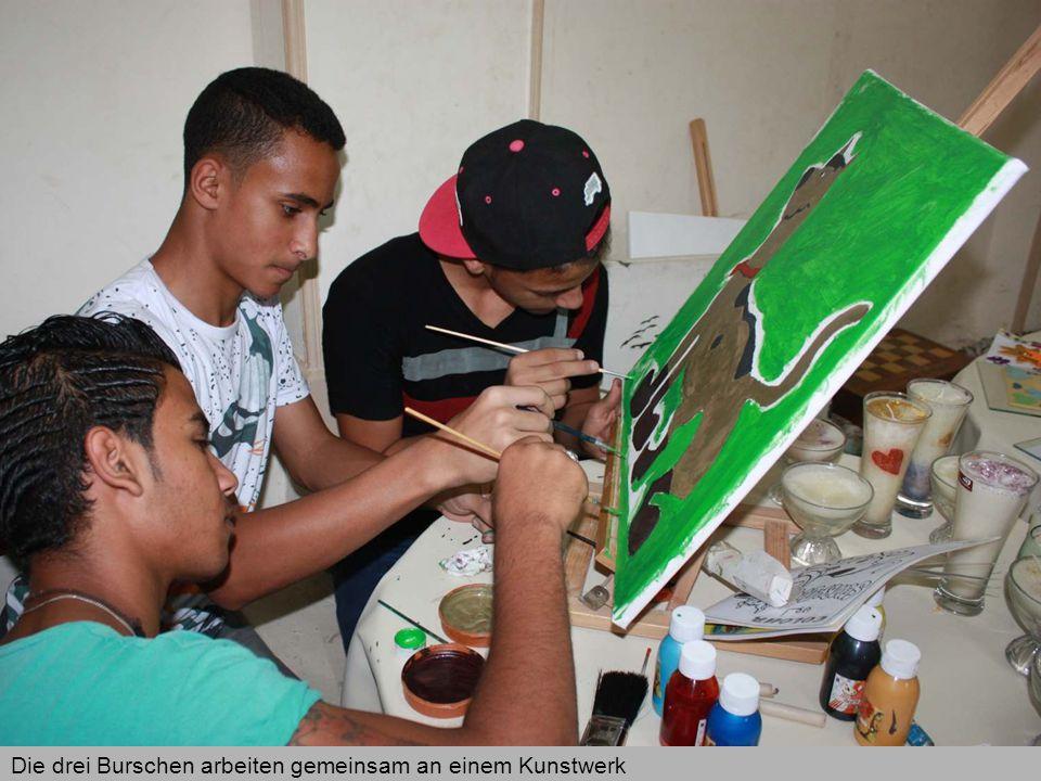 Die drei Burschen arbeiten gemeinsam an einem Kunstwerk