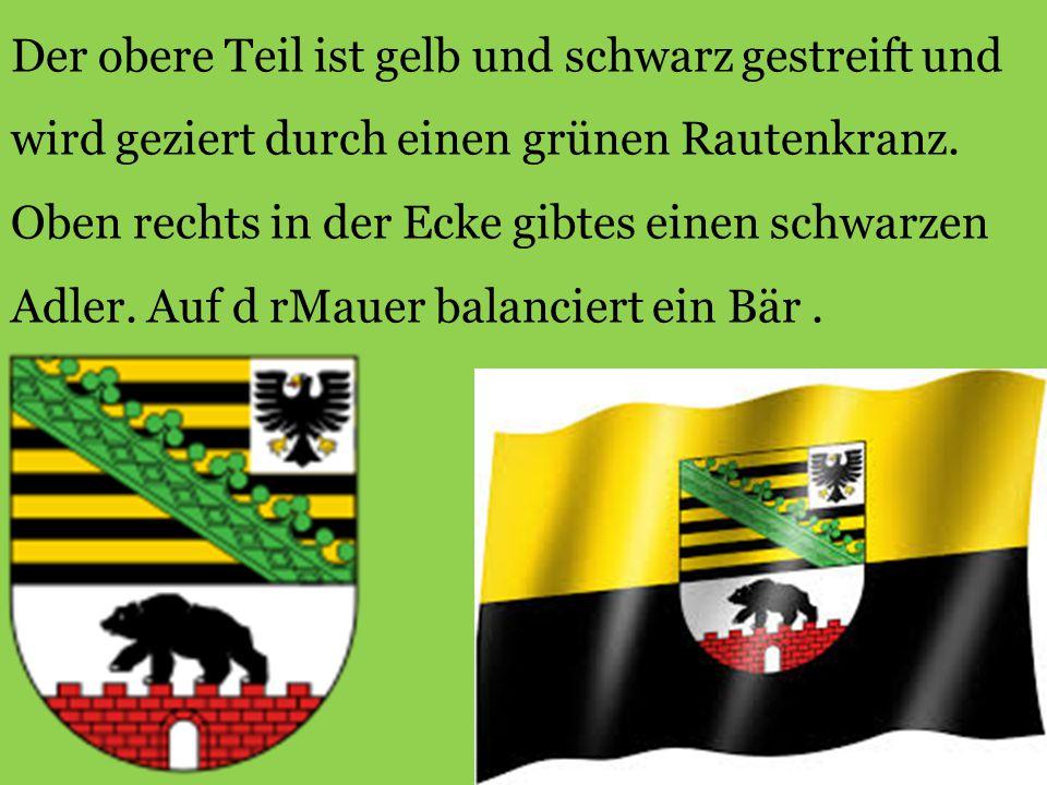 Der obere Teil ist gelb und schwarz gestreift und wird geziert durch einen grünen Rautenkranz. Oben rechts in der Ecke gibtes einen schwarzen Adler. A