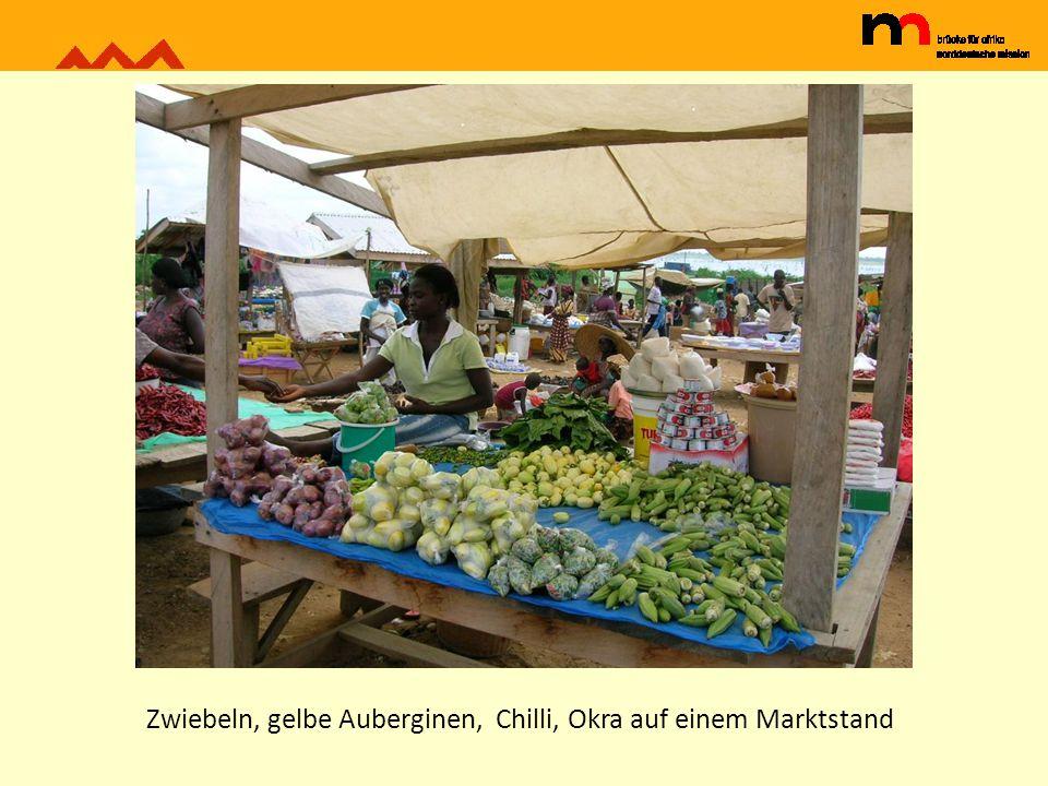 Zwiebeln, gelbe Auberginen, Chilli, Okra auf einem Marktstand