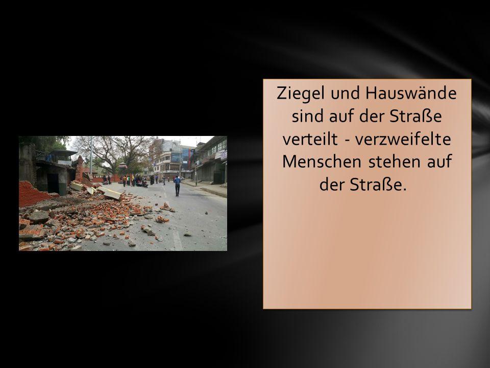 Ziegel und Hauswände sind auf der Straße verteilt - verzweifelte Menschen stehen auf der Straße.