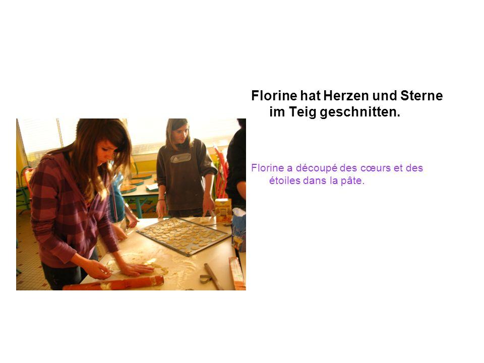 Florine hat Herzen und Sterne im Teig geschnitten. Florine a découpé des cœurs et des étoiles dans la pâte.