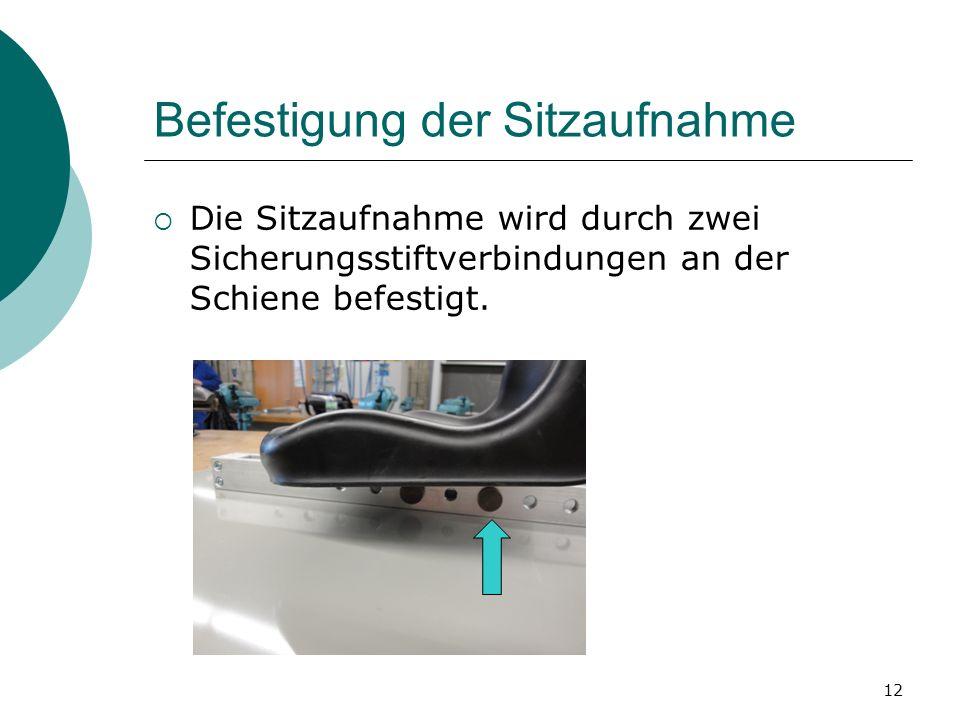 12 Befestigung der Sitzaufnahme Die Sitzaufnahme wird durch zwei Sicherungsstiftverbindungen an der Schiene befestigt.