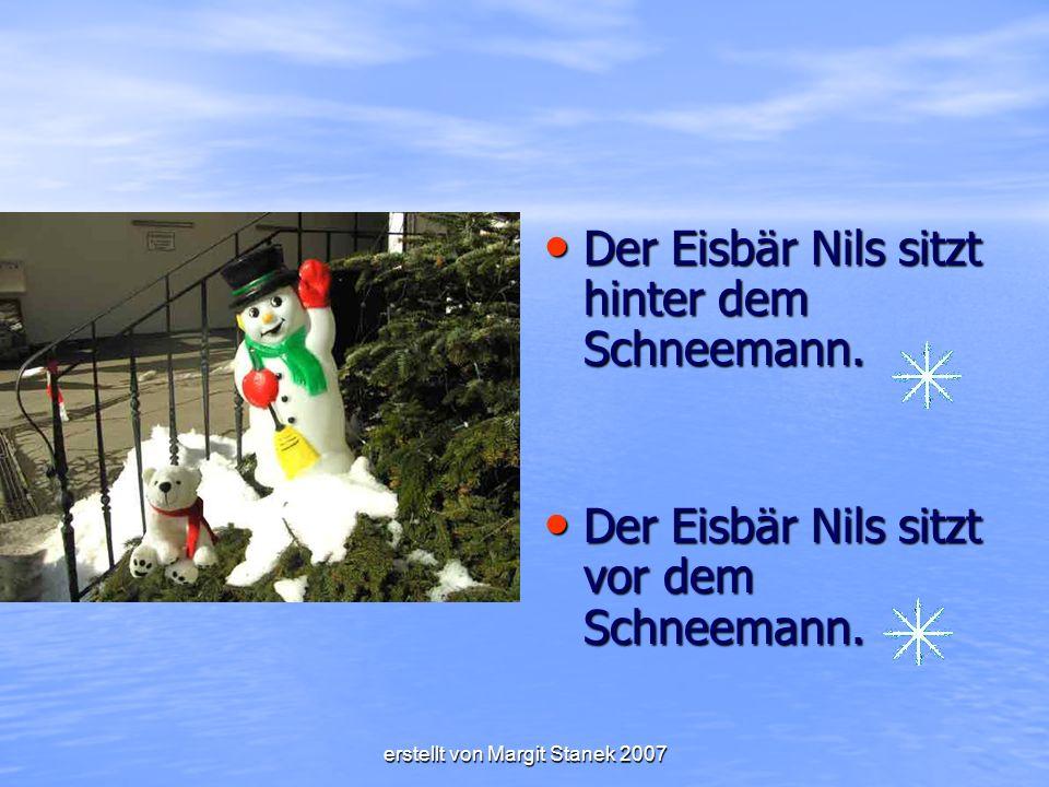 Der Eisbär Nils sitzt hinter dem Schneemann.Der Eisbär Nils sitzt hinter dem Schneemann.