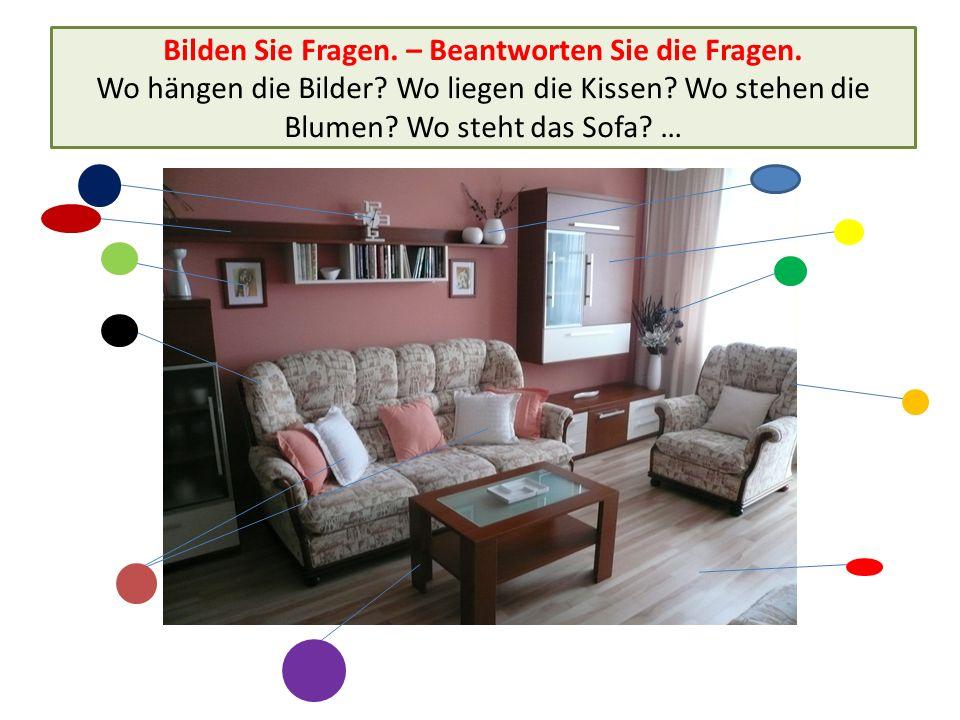 Bilden Sie Fragen. – Beantworten Sie die Fragen. Wo hängen die Bilder? Wo liegen die Kissen? Wo stehen die Blumen? Wo steht das Sofa? …