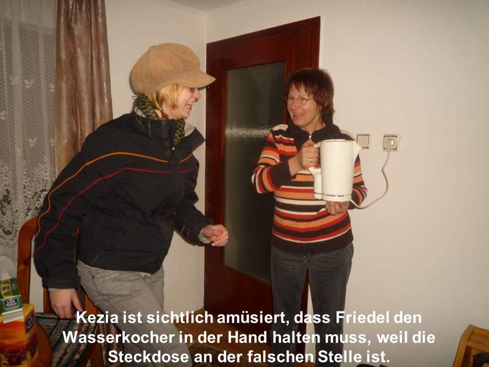 Kezia ist sichtlich amüsiert, dass Friedel den Wasserkocher in der Hand halten muss, weil die Steckdose an der falschen Stelle ist.