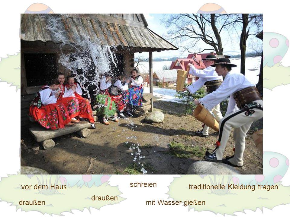 vor dem Haus draußen traditionelle Kleidung tragen mit Wasser gießendraußen schreien