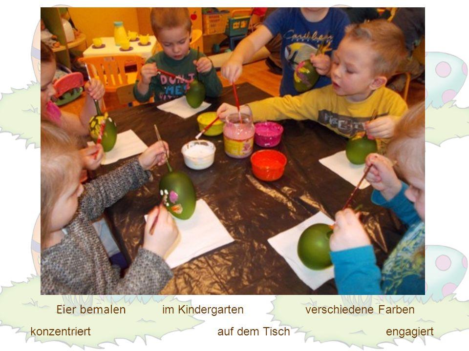 Eier bemalen engagiert verschiedene Farben auf dem Tischkonzentriert im Kindergarten