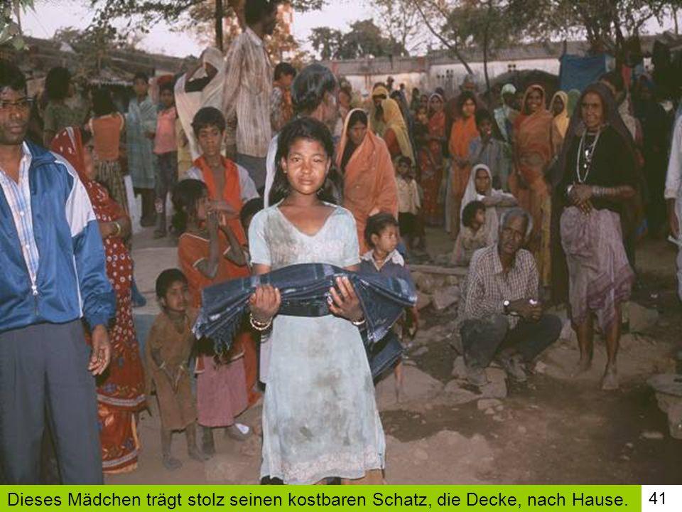 41 Dieses Mädchen trägt stolz seinen kostbaren Schatz, die Decke, nach Hause.