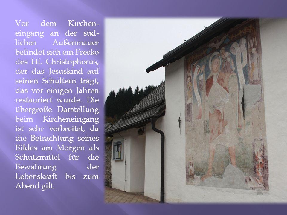 Vor dem Kirchen- eingang an der süd- lichen Außenmauer befindet sich ein Fresko des Hl. Christophorus, der das Jesuskind auf seinen Schultern trägt, d