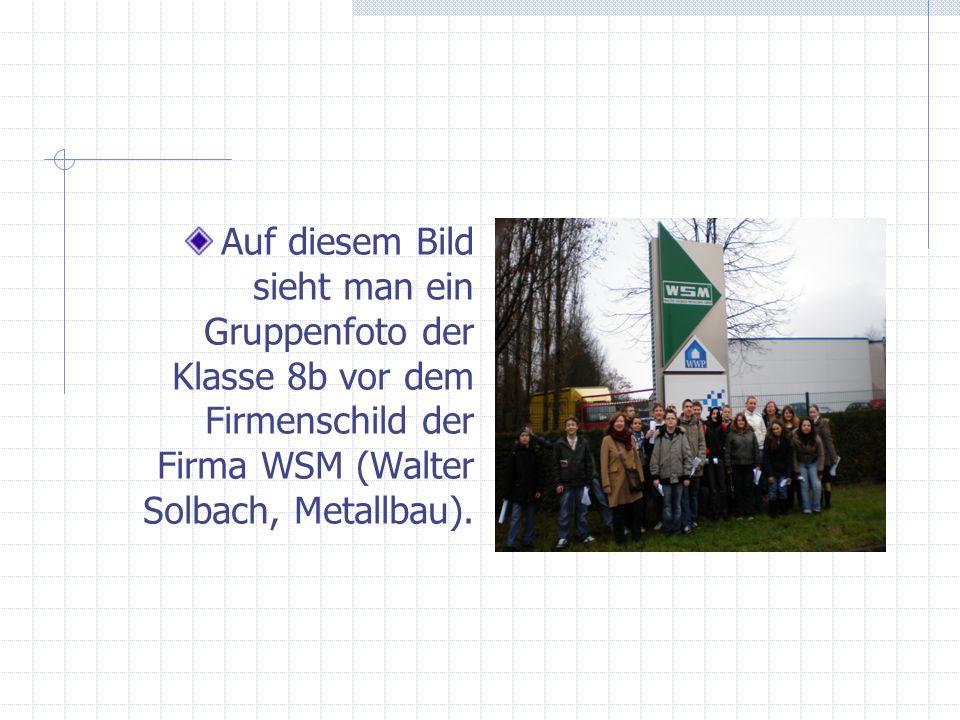 Auf diesem Bild sieht man ein Gruppenfoto der Klasse 8b vor dem Firmenschild der Firma WSM (Walter Solbach, Metallbau).