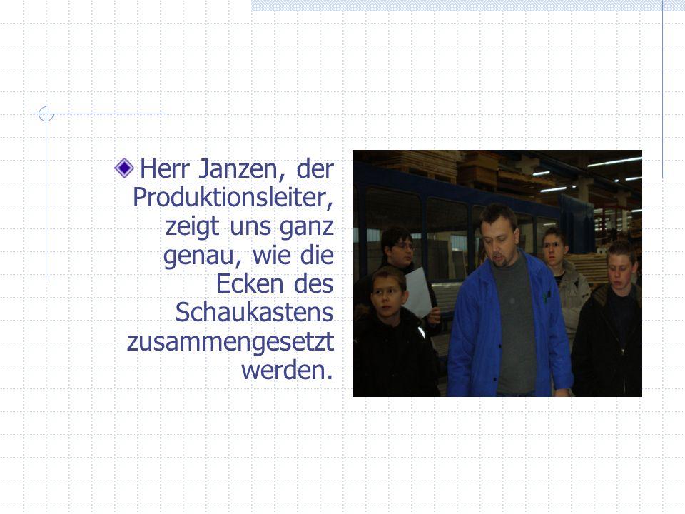Herr Janzen, der Produktionsleiter, zeigt uns ganz genau, wie die Ecken des Schaukastens zusammengesetzt werden.