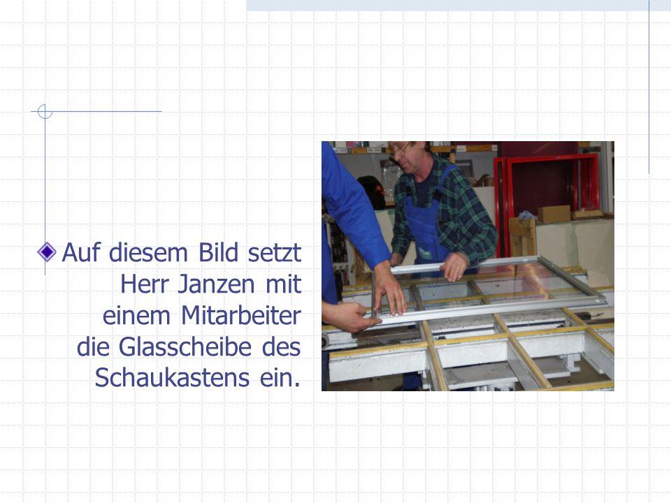 Auf diesem Bild setzt Herr Janzen mit einem Mitarbeiter die Glasscheibe des Schaukastens ein.