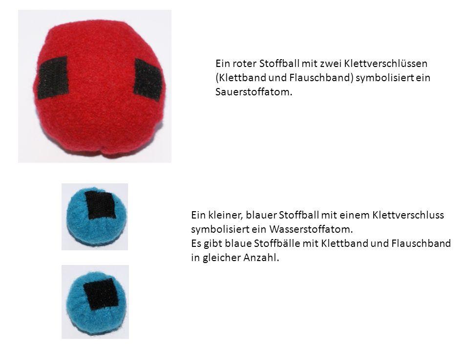 Ein roter Stoffball mit zwei Klettverschlüssen (Klettband und Flauschband) symbolisiert ein Sauerstoffatom. Ein kleiner, blauer Stoffball mit einem Kl