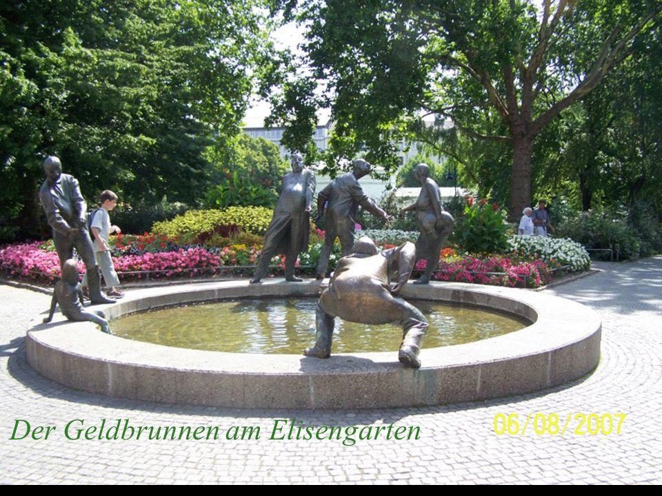 Auf dem Beckenrand der kreisrunden Brunnenanlage stehen lebensgroße Figuren, die alle etwas mit Geld zu tun haben.